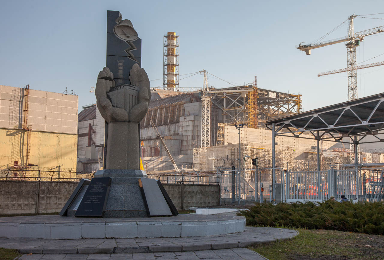 Monument dedicated to those who died during Chernobyl accident. Chernobyl reactor 4 in the background with sarcophagus falling apart behind it.